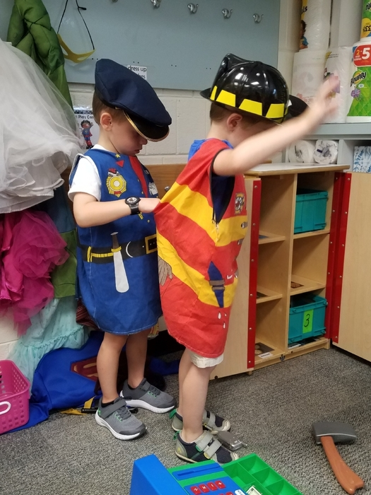 Not only are they dressed as a community helper, they are helping each other get dressed up.