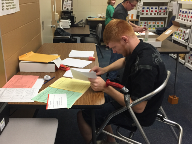 Joe working in the PAES lab organizing paperwork.