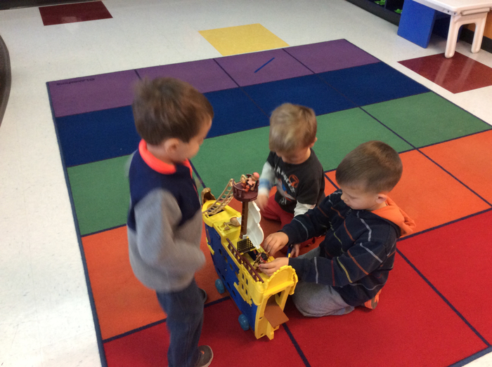 AM students playing with a Pirate Ship toy in the Block Center.