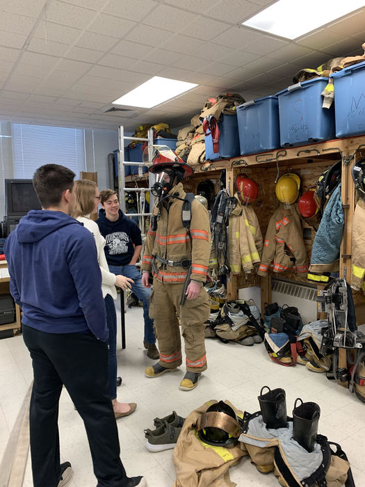 OHS Student trying on some gear from the Fire Science Program