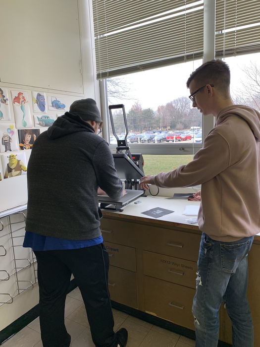 OHS students using the printing press in the Graphic Design and Video Production room