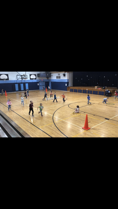 Students running laps to earn cups.