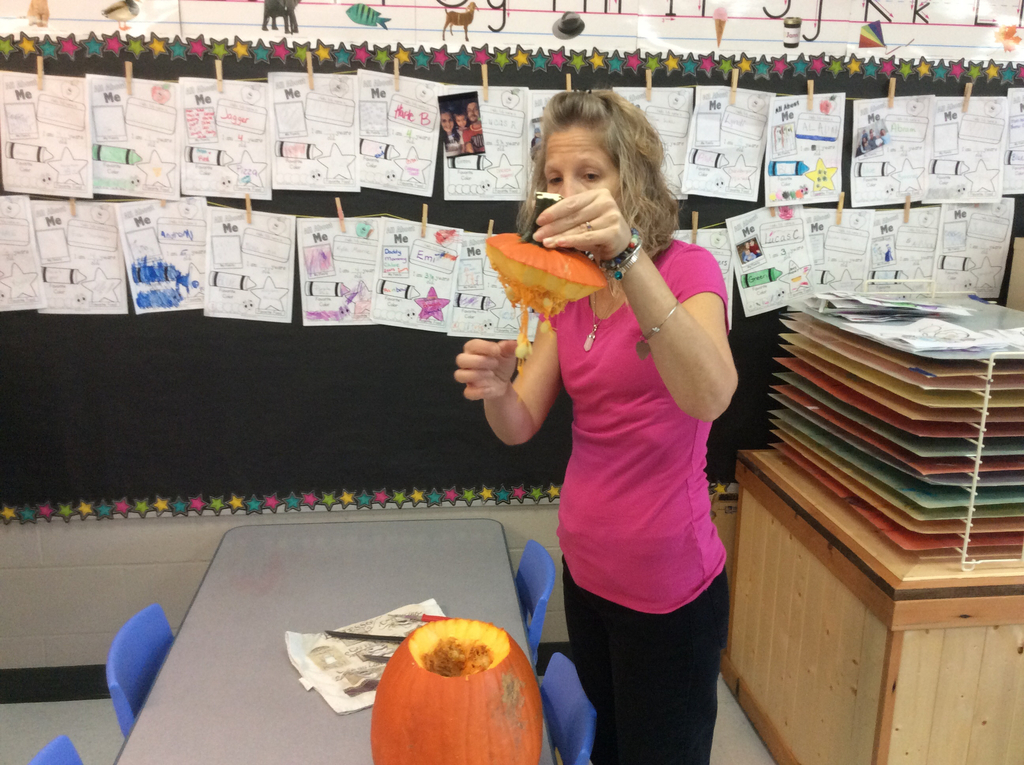 Ms. Lisa talking with the morning friends about what the inside of the pumpkin looks like.